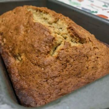 Fresh loaf of cream cheese banana nut bread in bread ban.