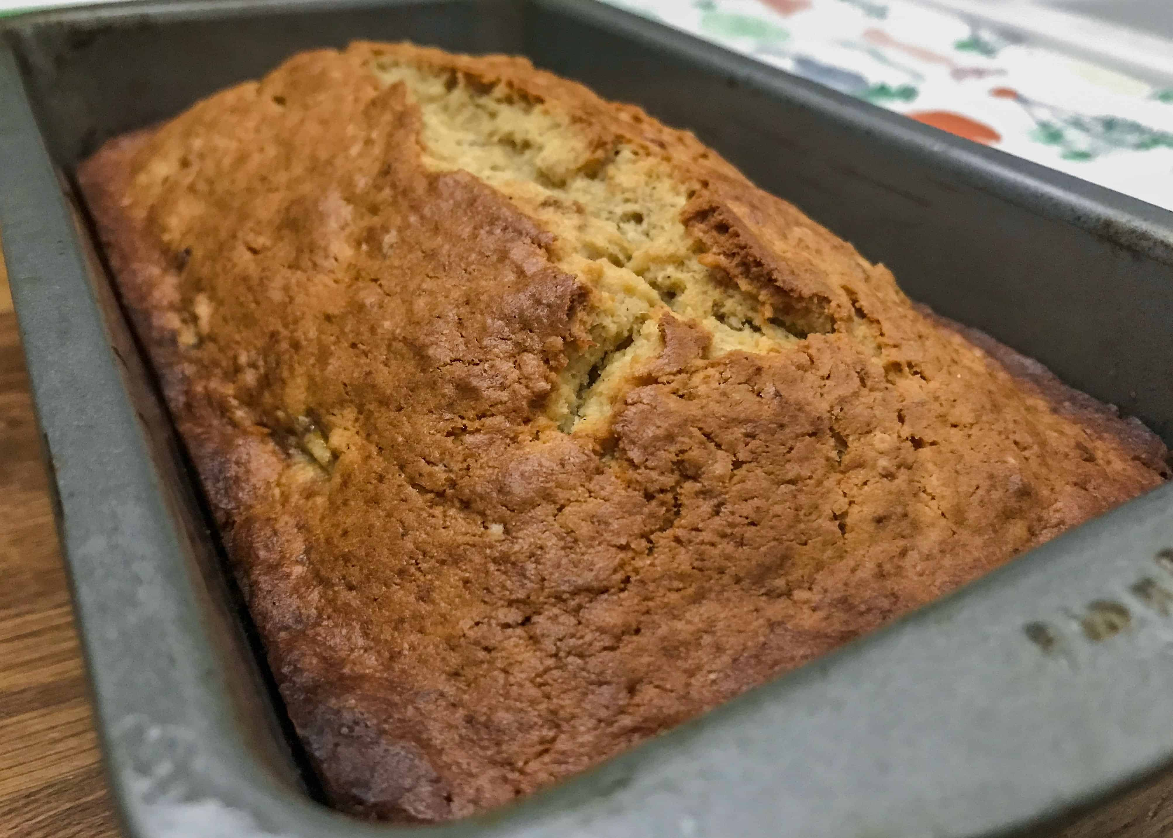 Fresh loaf of cream cheese banana nut bread in bread ban.